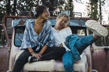 Friends sitting on a broken truck, having fun - KKAF02205