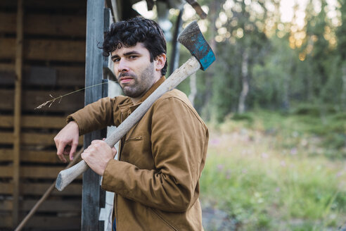 Young man holding axe, leaning against wood house - KKAF02211