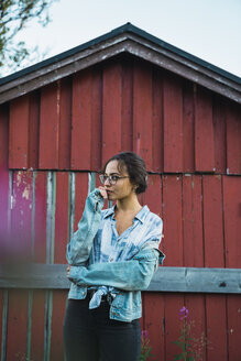 Portrait of a young woman standing in front of a red wood hut - KKAF02217