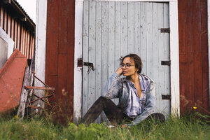 Portrait of a young woman sitting in grass in front of a wooden shack - KKAF02220
