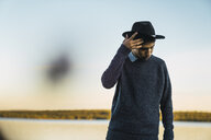 Portrait of a young man with hat at  a lake - KKAF02223