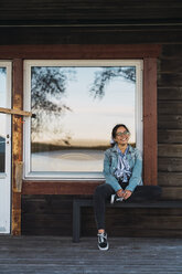 Happy young woman sitting on veranda of a wooden house - KKAF02226
