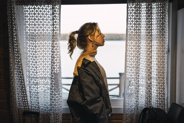 Portrait of a young woman standing in a room with a window - KKAF02232
