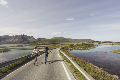 Young women walking on an empty road, Lapland, Norway - KKAF02241