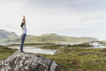 Young woman standing in nature, stretching, Lapland, Norway - KKAF02250