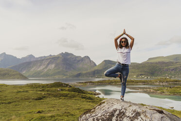 Young woman practicing yoga in nature, Lapland, Norway - KKAF02253
