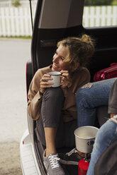 Friends sitting in a camper, taking a break, drinking coffee - KKAF02262