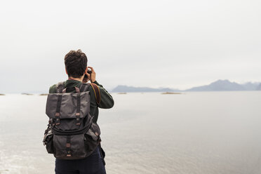 Young man taking pictures of a lake in Vesteralen Island, Lapland, Norway - KKAF02265
