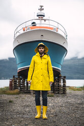 Young man standing in front of a ship, wearing rain clothes, Lapland, Norway - KKAF02283