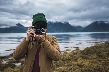 Young man with woolly hat taking pictures with camera - KKAF02292