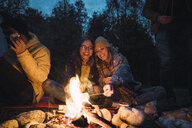 Group of friends sitting at a campfire, roasting marshmallows - KKAF02295