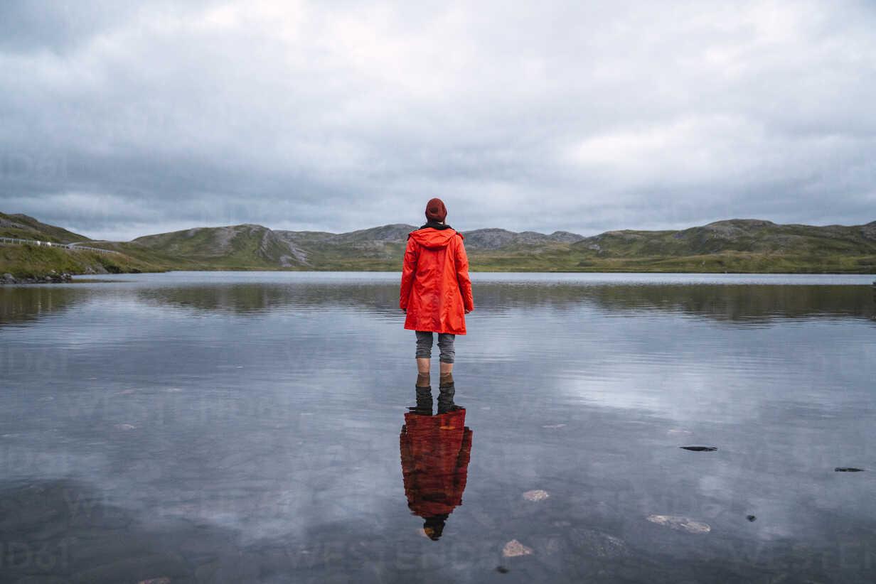 Young man standing ankle deep in water, looking at distance, rear view - KKAF02310 - Kike Arnaiz/Westend61