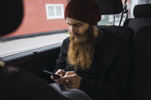 Bearded young man sitting on back seat of a car checking cell phone - KKAF02313