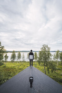 Finland, Lapland, man standing on roof of a house at a lake - KKAF02316