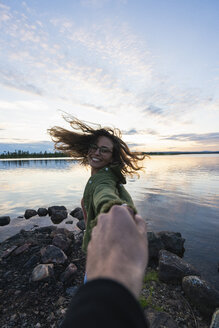Finland, Lapland, happy young woman holding man's hand at the lakeside at twilight - KKAF02322