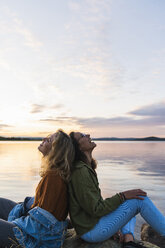 Finland, Lapland, two happy young women sitting back to back at the lakeside at twilight - KKAF02328