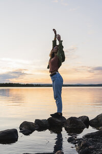 Finland, Lapland, woman standing at the lakeside at twilight - KKAF02334