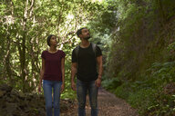 Spain, Canary Islands, La Palma, couple walking through a forest looking around - PACF00147