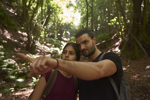 Spain, Canary Islands, La Palma, couple in a forest with man pointing his finger - PACF00153