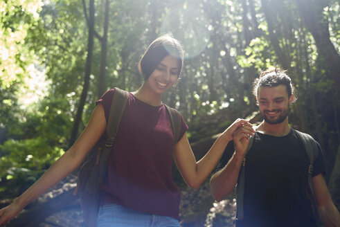 Spain, Canary Islands, La Palma, smiling couple walking hand in hand through a forest - PACF00156
