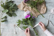 Woman's hand binding bunch of flowers - JUNF01337