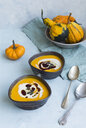 Two bowls of homemade Hokkaido pumpkin soup garnished with cream, pumpkin seed oil and pumpkin seed - JUNF01352