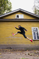 Dynamic athlete jumping in front of a yellow wood house - KKAF02352