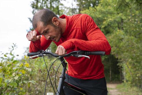 Exhausted mountain biker taking a break in nature - KKAF02370