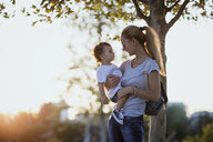 Mother holding her little son outdoors at sunset - AZOF00065