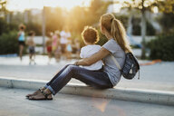 Mther sitting with her little son on a square at sunset - AZOF00068