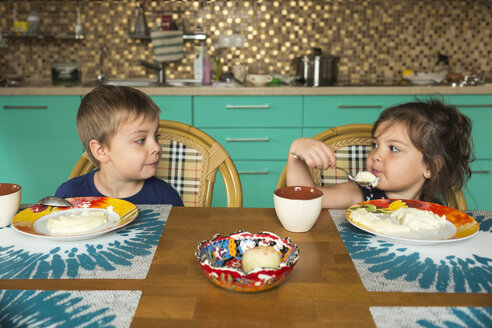 Portrait of boy and his little sister eating breakfast in the kitchen - VGF00001