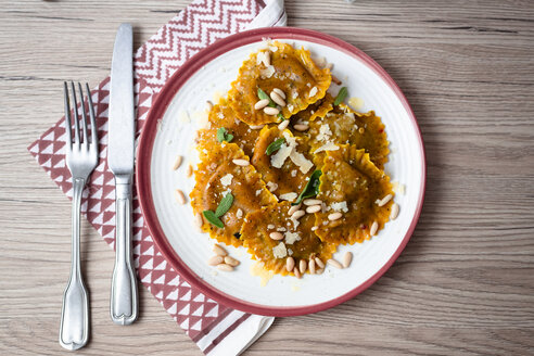 Plate of pumpkin ravioli with sage leaves, parmesan and pine nuts - GIOF04550