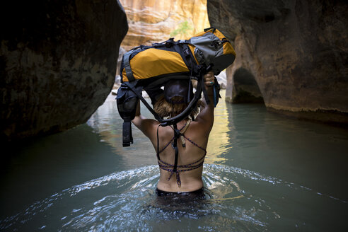 A woman explores the Narrows in Zion National Park, Utah. - AURF07670