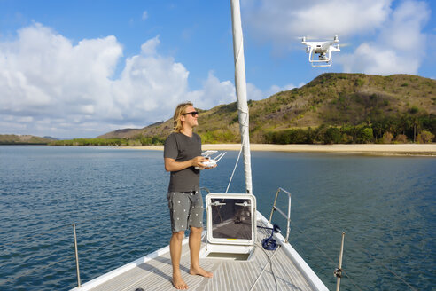 Man flying drone on yacht - AURF07697