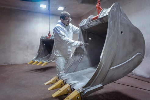 Spray painter cleaning digger bucket in spray booth in engineering factory - CUF43822
