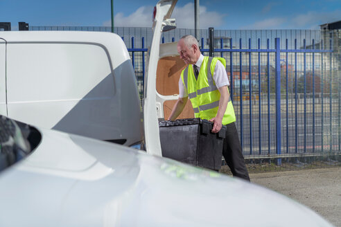 Senior delivery driver loading all electric van - CUF43840