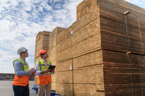 Workers with stacks of timber in storage at port - CUF43987