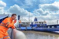 Ship's worker using walkie talkie to communicate with loading ferry ships in port in background - CUF43999