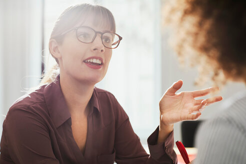 Businesswoman in office talking to colleague - CUF44032