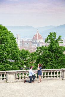Young man proposing to woman, Santa Maria del Fiore in background, Florence, Toscana, Italy - CUF44086