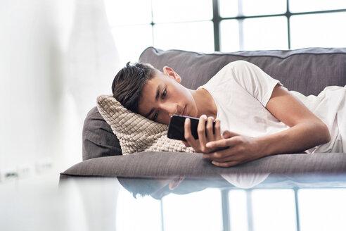 Teenage boy lying on sofa looking at smartphone - CUF44146