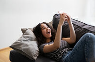 Teenage girl relaxing on sofa laughing at smartphone - CUF44149