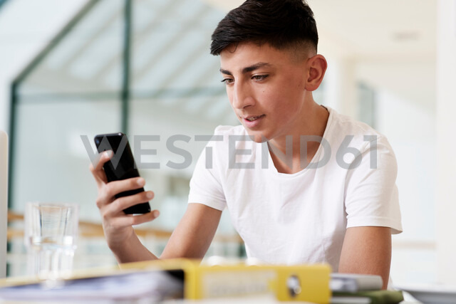Teenage schoolboy at classroom desk looking at smartphone - CUF44152 - T2 Images/Westend61