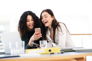 Teenage schoolgirls at classroom desk laughing at smartphone - CUF44155