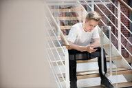 High school boy sitting on school stairway looking at smartphone - CUF44164