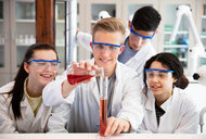 Students pouring sample into flask in laboratory - CUF44173