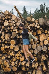Happy young woman balancing on stack of wood - KKAF02378