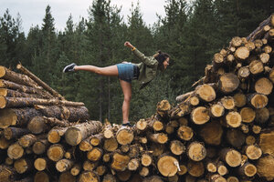 Young woman standing on one leg on stack of wood - KKAF02384