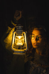 Young woman holding storm lantern in the dark - KKAF02402