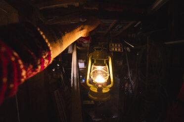 Hand holding storm lantern in a dark chamber - KKAF02405